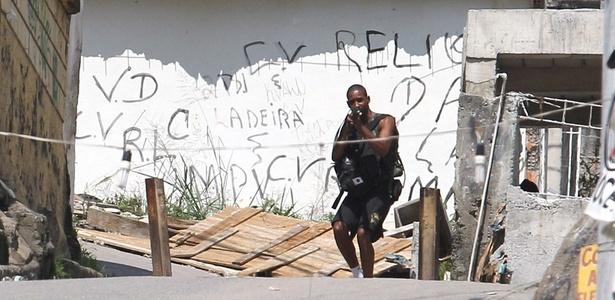 Homem armado aparece em uma das entradas do Complexo do Alemão; veja mais imagens - Júlio César Guimarães/UOL