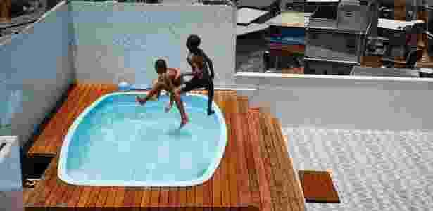 Crianças brincam em piscina da casa encontrada pelos policiais no Complexo do Alemão - Marcelo de Jesus/UOL