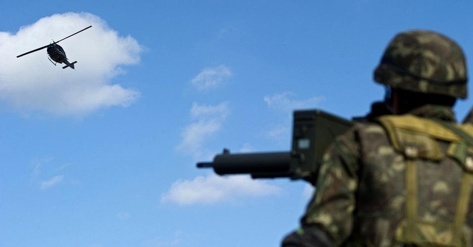 Helicóptero sobrevoa o Complexo do Alemão enquanto é observado por soldado do Exército