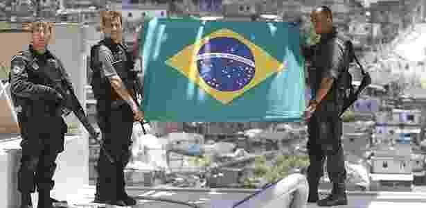 Policiais seguram bandeira do Brasil na parte superior de teleférico em obras no alto do Alemão - Alexandro Auler/AE