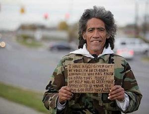 O sem-teto Ted Williams pede um trocado na rua em troca de uma palhinha