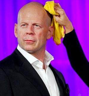 Funcionário do museu de cera Madame Tussauds de Londres dá os toques finais na estátua de Bruce Willis
