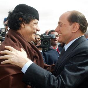 Em foto de 2004, o ex-premiê italiano Silvio Berlusconi (dir.) é cumprimentado pelo então ditador líbio Muammar Gaddafi, que foi morto em outubro de 2011 por rebeldes - Reuters
