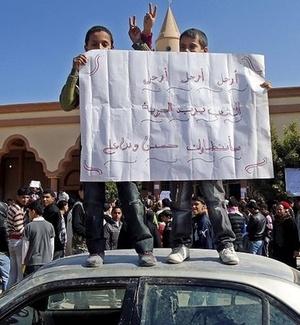 Imagem divulgada hoje mostra crianças em cima de carro protestando contra o governo do ditador líbio Muammar Gaddafi na cidade de Tobruk. No cartaz está escrito: