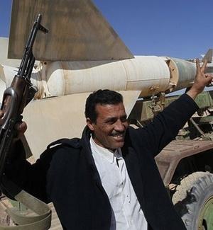 Militar líbio exibe seu fuzil AK-47 em frente a um míssil antiaéreo abandonado em Tobruk; parte das Forças Armadas do país desertaram e se uniram aos manifestantes