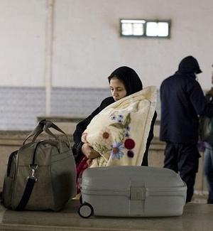 Após deixar a Líbia, mulher e seu filho aguardam para pegar sua bagagem no lado da Tunísia na região de fronteira entre os dois países