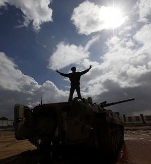 Homem faz o sinal da vitória em cima de um tanque do Exército em Benghazi, na Líbia