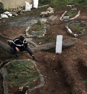 Homem reza em meio a túmulos de vítimas mortas durante os protestos em Darnah, na Líbia