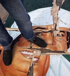 um ato de desrespeito a Muammar Gaddafi, líbio pisa em retrato destruído do ditador, na região do aeroporto La Braq, na Líbia