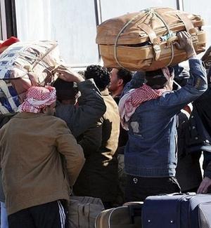 Egípcios residentes na Líbia sobem em ônibus em Ras El Jadir, na fronteira da Líbia