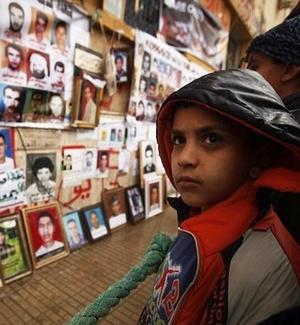 Garoto observa fotografias de líbios mortos ou desaparecidos em uma rua de Benghazi