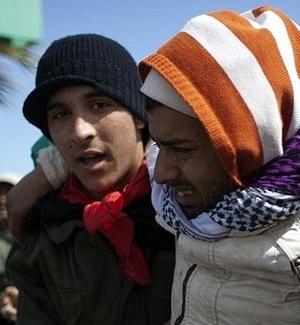 Rebelde é carregado após ser atingido por ataque a bomba de forças leais a Muammar Gaddafi