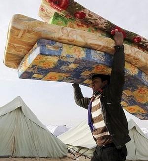 Refugiado carrega colchões em Ras Ajdir, fronteira entre Líbia e Tunísia
