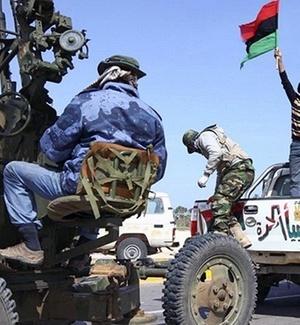 Rebelde segura bandeira da Líbia usada pelos opositores de Gaddafi, em Ras Lanuf