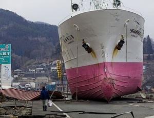 Homem passa por navio na rua em um porto na cidade devastada de Kesennuma