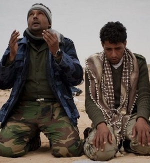Rebeldes líbios fazem oração perto da cidade de Benghazi, onde se concentram os grupos insurgentes