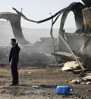 Sobrevivente caminha por armazém destruído pelos bombardeiros em Trípoli, capital da Líbia