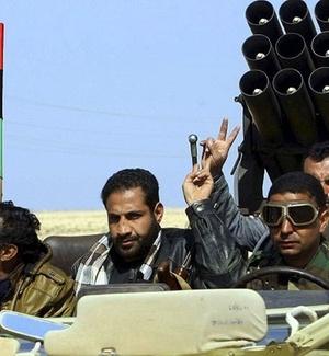 Rebeldes líbios fazem sinal de vitória, na estrada entre Ajdabiya e Benghazi, na Líbia