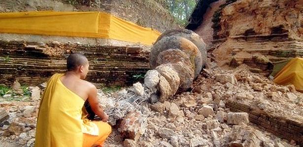 Monge budista tailandês observa construção destruída pelo terremoto
