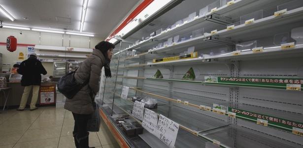 Mulher olha prateleira de supermercado vazia no distrito de Miyagi, no Japão - Shizuo Kambayashi/AP