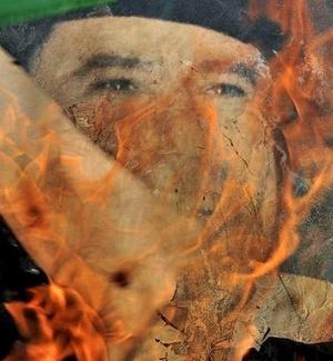 Retrato do ditador líbio Muammar Gaddafi é queimado por rebeldes na cidade de Bin Jawad
