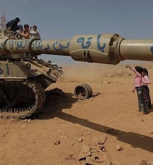 Crianças olham enquanto líbios inspecionam veículo militar das forças de Gaddafi, destruído pelas forças da Otan