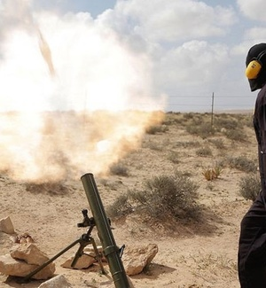 Rebeldes líbios atiram contras as forças de seguranças, em estrada próxima a Brega