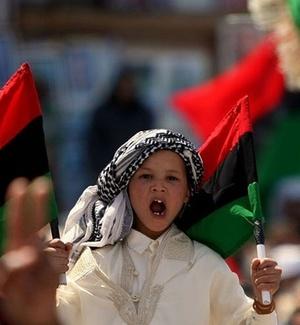 Garoto líbio levanta bandeira rebelde durante manifestação anti-Gaddafi em Benghazi
