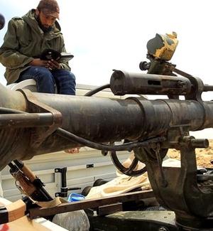 Rebelde líbio lê o Corão perto da entrada da cidade Ajdabiyah