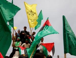 Palestinos agitam bandeiras do Hamas e do Fatah durante comemoração pela reconciliação entre os dois grupos palestinos, na Cidade de Gaza