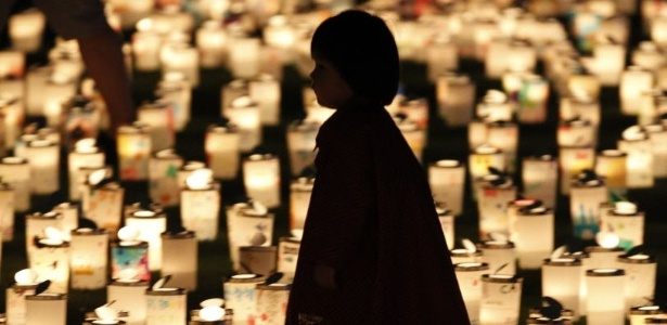Menina caminha entre recipientes iluminados por 2.500 velas durante evento para lembrar as vítimas do terremoto seguido de tsunami que atingiu o Japão em março