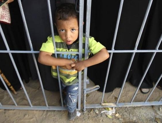 Menino palestino espera para atravessar fronteira ao sul da Faixa da Gaza, nesta segunda