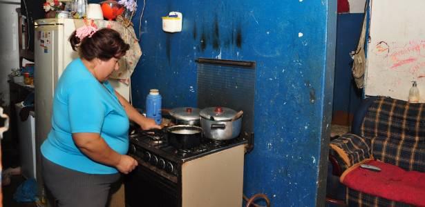 Romilda Rodrigues cozinha na casa improvisada dentro de um banheiro em Presidente Epitácio (SP)