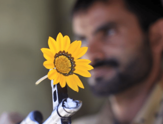 Homem segura rifle AK-47 com flor presa enquanto faz segurança de rua próxima a protestos pelo julgamento do presidente Ali Abdullah Saleh, do Iêmen
