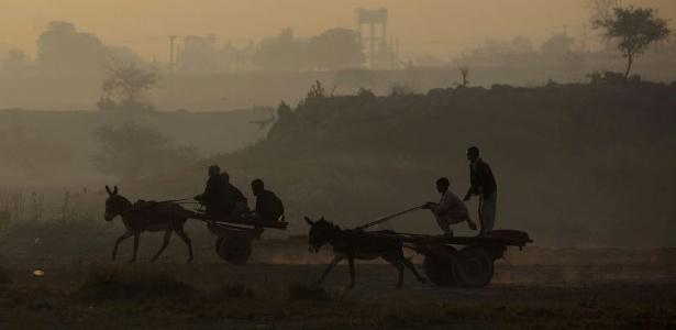 Paquistaneses andam com carros puxados por burros durante o nascer do sol nos arredores de Islamabad, capital do Paquistão