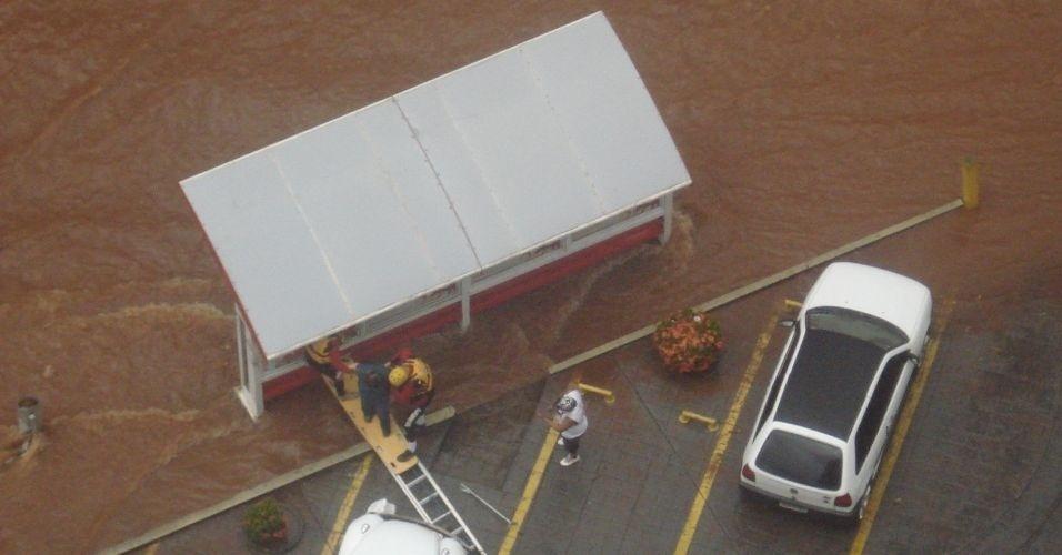 10.mar.2012 - Pedestres que ficaram ilhados em um ponto de ônibus são resgatados durante alagamento provocado pelo temporal que atingiu São José do Rio Preto (SP), neste sábado