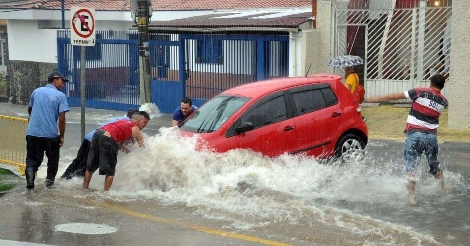 11.fev.2012 - Em ponto de alagamento na rua Água Fria no Mandaqui, na zona norte de São Paulo, homens tentam empurrar carro. Veja aqui mais fotos de chuvas pelo Brasil