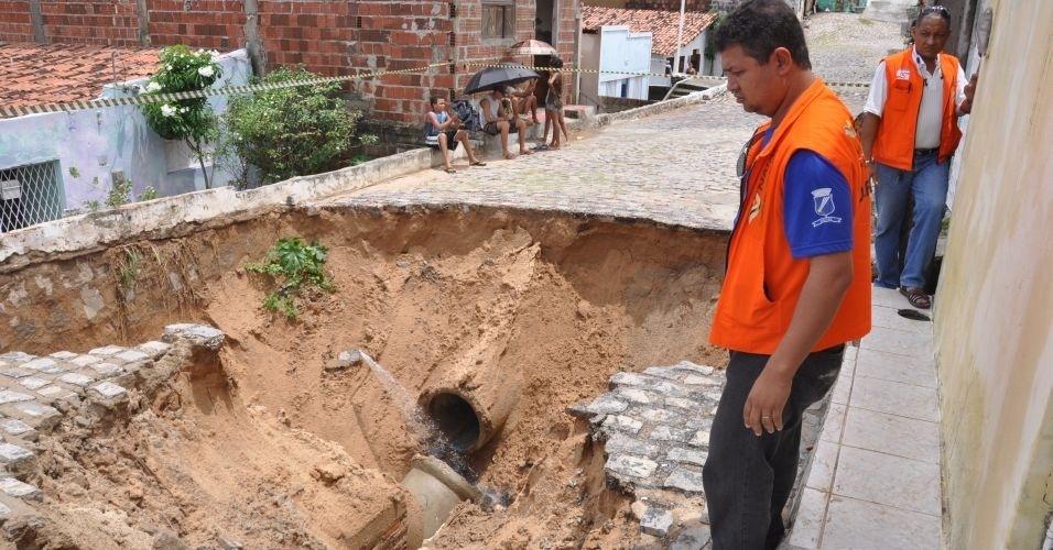14.mar.2012 - Funcionários da defesa civil resgatam criança, nesta quarta-feira, no trecho da rua Augusto Alves, bairro Mãe Luiza, em Natal (RN), onde um rompimento de tubulação abriu uma cratera na rua, durante as chuvas que atingem a cidade