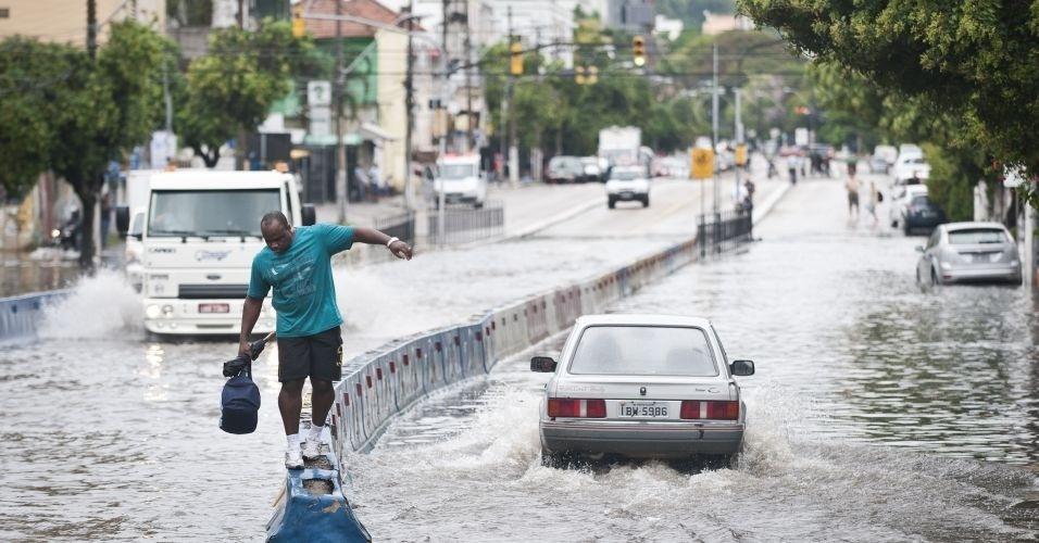 14.mar.2012 - Homem se arrisca em meio a alagamento em Porto Alegre. Uma forte chuva atingiu a capital gaúcha, deixando mais de 50 mil pessoas sem luz na região metropolitana. A estimativa é de que choveu, apenas pela manhã, 60% do volume esperado para todo o mês de março