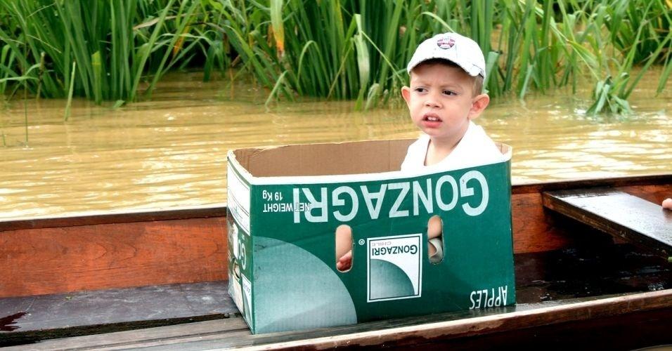 27.fev.2012 - Criança é colocada dentro de uma caixa de maçãs para ser transportada de barco. As enchentes no Acre afetam mais de 100 mil pessoas no Estado