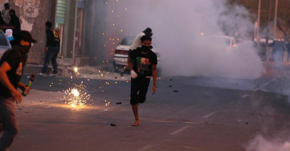 Bareinita foge de bomba de gás lacrimogêneo lançada pela polícia no vilarejo de Diraz, a oeste de Manama, capital do Bahrein