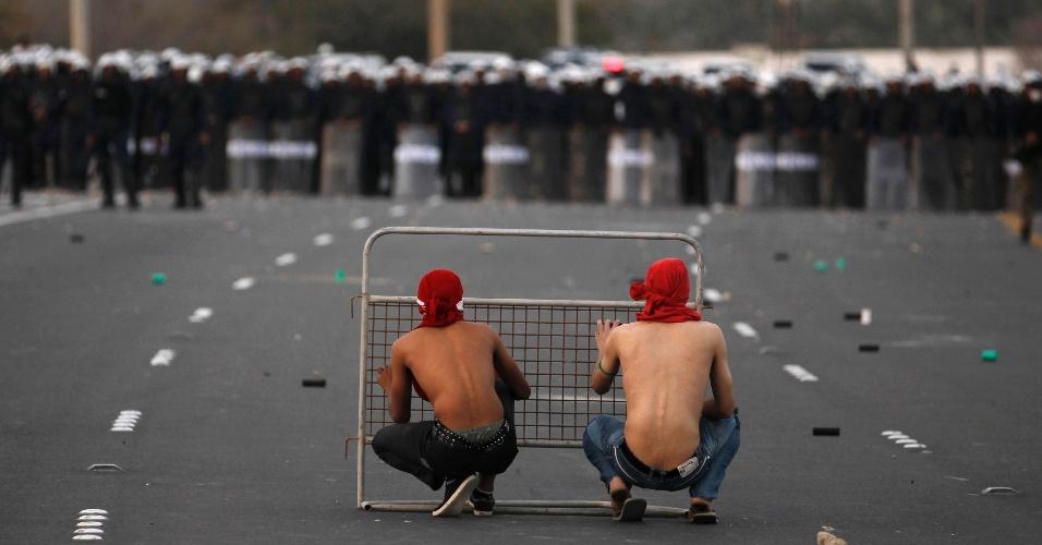 Bareinitas antigoverno tentam se proteger da polícia, que faz um cordão de segurança em Manama, capital do Bahrein
