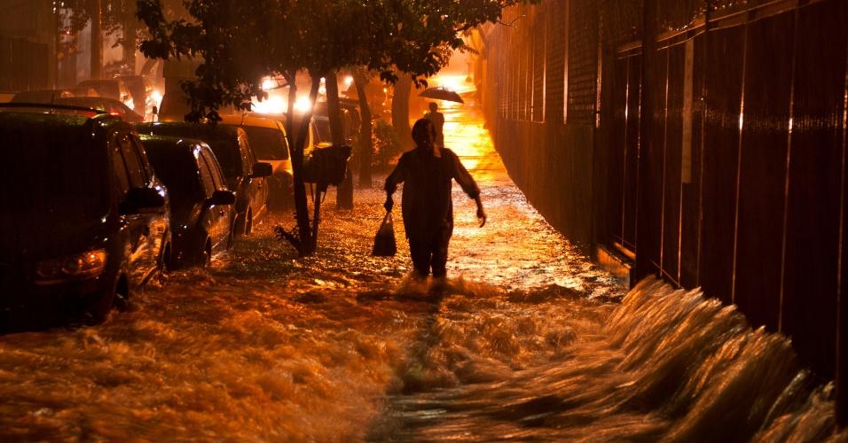 Mulher tenta passar por alagamento da rua Raul Pompeia, próximo à esquina com a rua Venâncio Aires, no bairro Vila Pompeia, zona oeste de São Paulo, nesta quinta-feira (15)