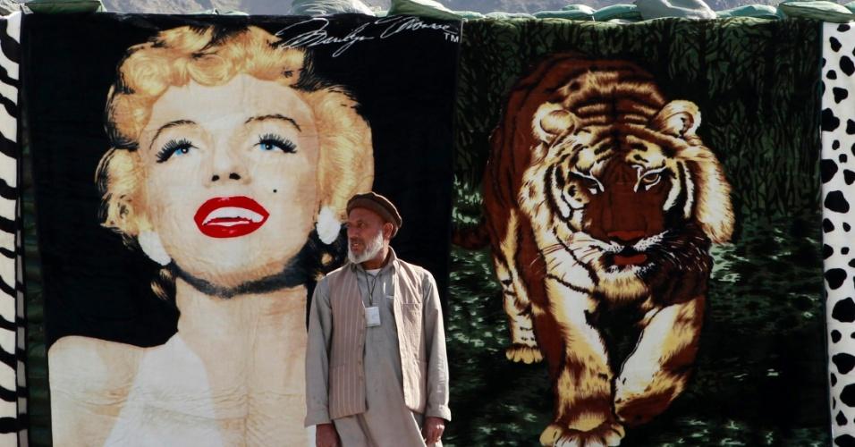 Vendedor espera por clientes em frente a cobertor com a imagem da atriz Marilyn Monroe em bazar na província de Kunar, no Afeganistão