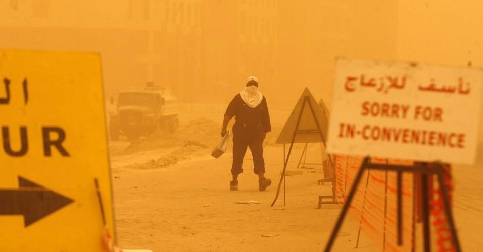 Em meio a tempestade de areia, homem caminha próximo de obra em  Al Kuait, no Kuait
