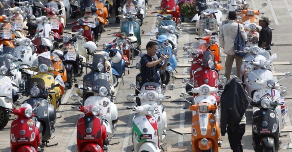 Homem é observado em evento que reúne apaixonados pela moto Vespa, na Tailândia