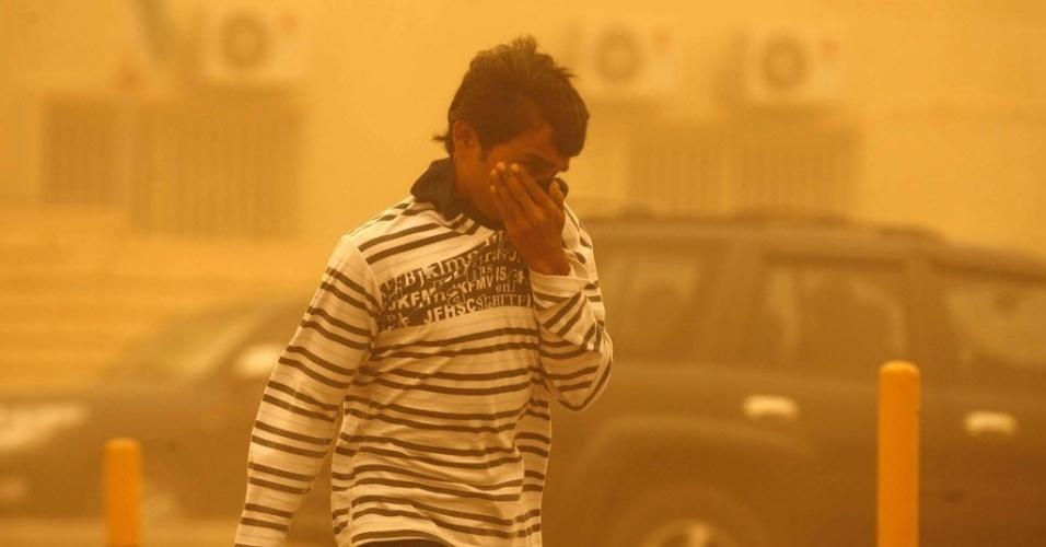 Homem kuaitiano tenta se proteger de tempestade de areia em Rawdatayn, ao norte de Al Kuait, no Kuait