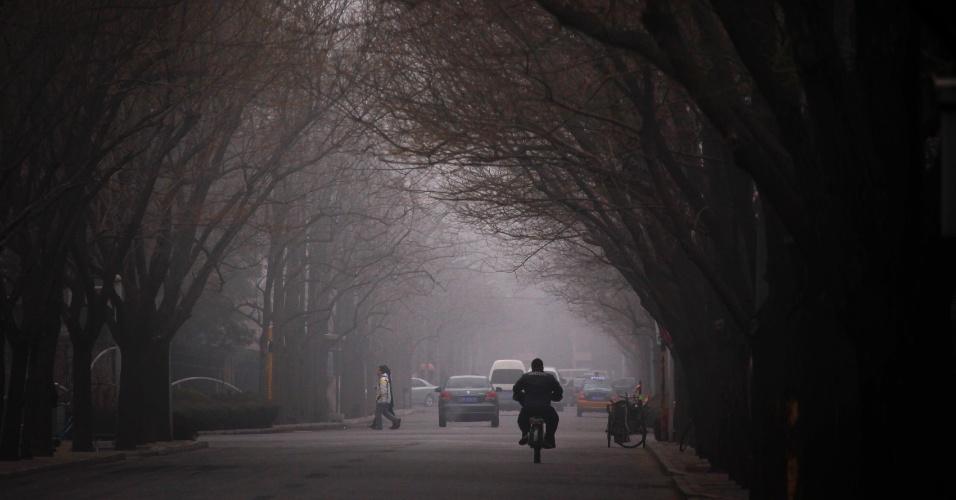 Motoristas e pedestres trafegam por uma estrada encoberta por uma camada de nevoeiro que cobriu Pequim (China), neste sábado (17). Mais de 23 voos foram cancelados por causa da neblina