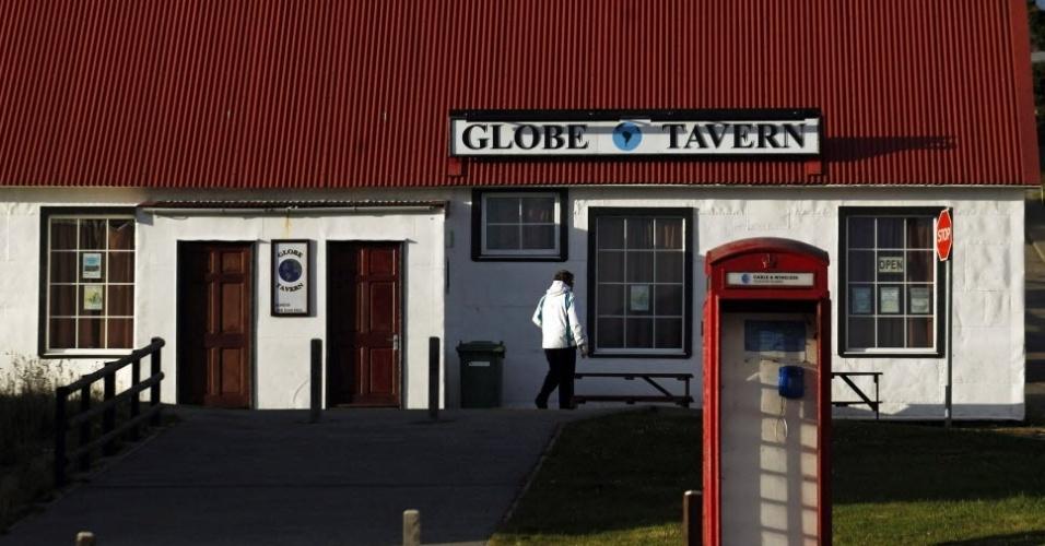 Mulher anda diante de taverna em Porto Stanley, principal cidade das ilhas Malvinas (ou Falklands, como os britânicos chamam sua possessão no Atlântico Sul)