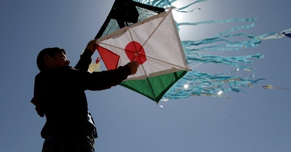 Garoto palestino empina em Gaza pipa que reúne as bandeiras do Japão e Palestina